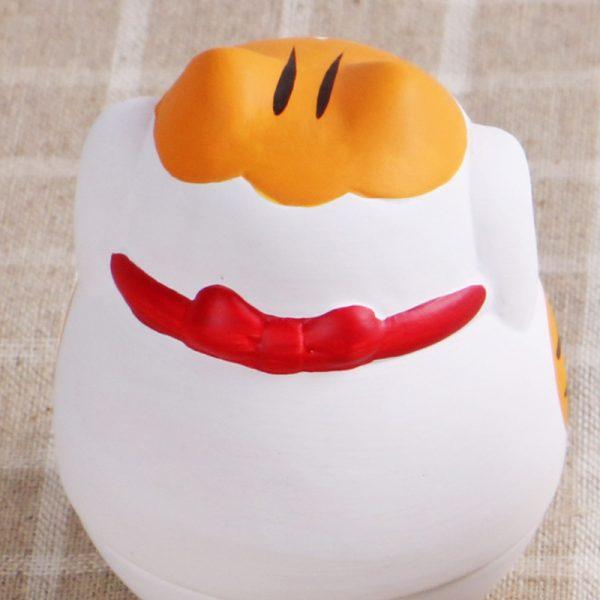 Maneki Neko japonés de cerámica y base redonda en color naranja.